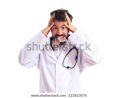 Frustrated doctor with pills over white background - stock photo