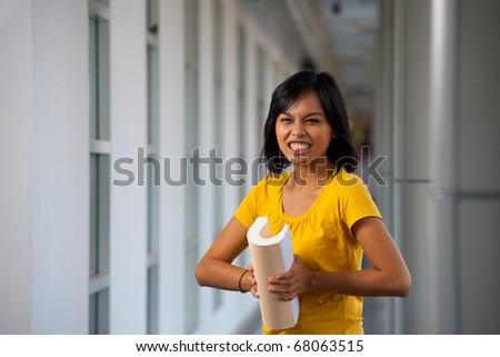 Frustrated female college student in yellow shirt bending abusing her textbook in anger standing in modern university corridor.  20s Asian Thai model of Chinese descent looking at camera