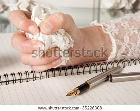 Frustrated hand squeezing a crumpled ball of paper - stock photo