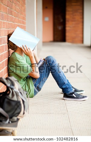 frustrated high school boy using book cover his face in school passage - stock photo