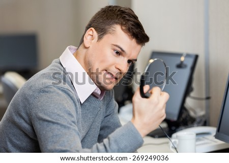 Frustrated male customer service representative holding headphones in office - stock photo