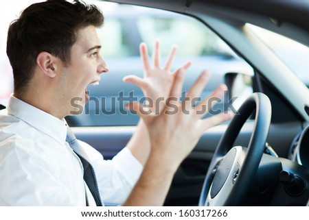 Frustrated man driving car - stock photo