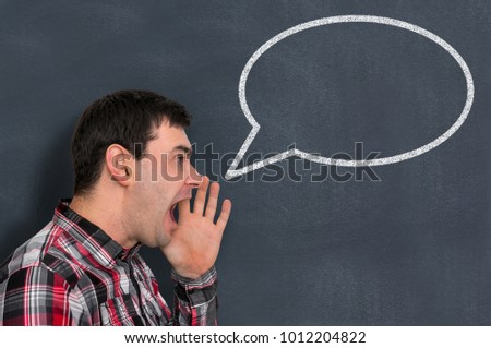 Frustrated man is screaming in class with drawn empty bubble on blackboard - education concept