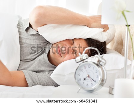 Frustrated man listening to his alarm clock while relaxing on his bed - stock photo