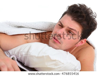 frustrated man lying in bed on white background