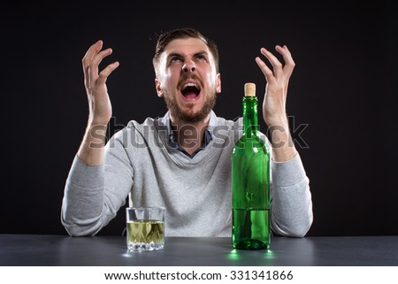Frustrated Man With Bottle On Black Background - stock photo