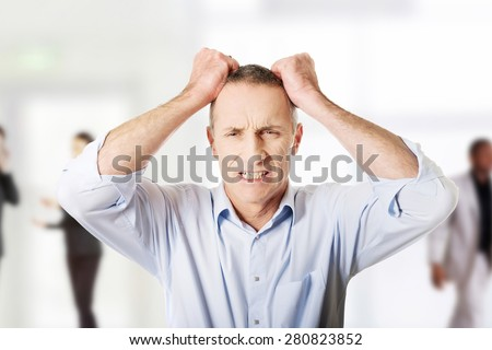 Frustrated mature man pulling his hair.  - stock photo