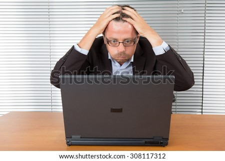 Frustrated middle aged businessman sitting at office desk - stock photo