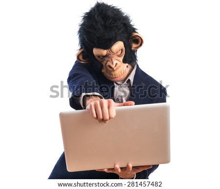 Frustrated monkey man holding a laptop - stock photo