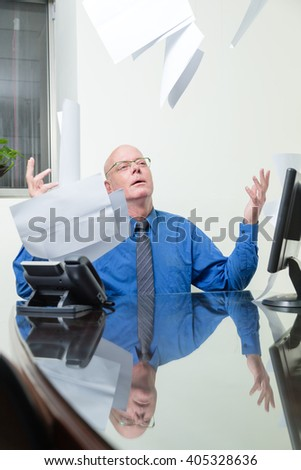 Frustrated office worker at desk throws paperwork in air - stock photo
