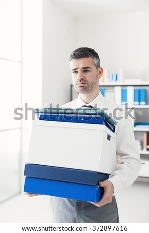Frustrated sad businessman carrying a load of boxes and paperwork in the office, relocation, stress and responsibility concept