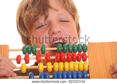 Frustrated schoolboy bites into abacus - stock photo