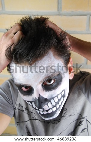 frustrated skeleton guy, portrait of a creepy skeleton guy perfect for Carnival (brick wall background) - stock photo