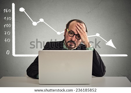 Frustrated stressed business man sitting at table in front of computer with financial market chart graphic going down on grey office wall background. Poor economy concept. Face expression, emotion - stock photo