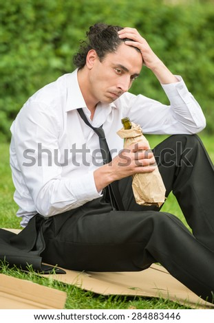 Frustrated unemployed man sitting at the lawn and drinking alcohol. Depression. - stock photo