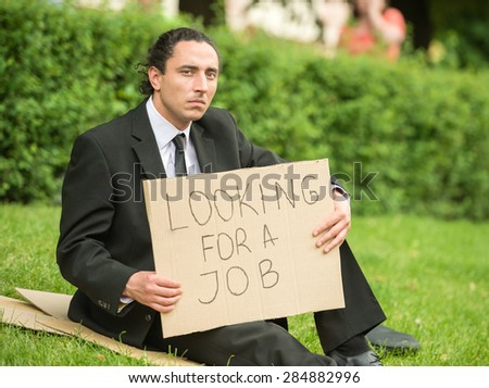 Frustrated unemployed man with sign sitting at the lawn. - stock photo