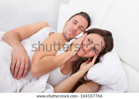 Frustrated Woman Disturbed With Man Snoring Behind Her - stock photo