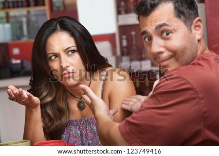 Frustrated woman gesturing with her hands arguing with man - stock photo