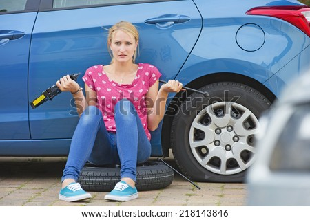 Frustrated Woman Trying To Change Flat tire On Car - stock photo