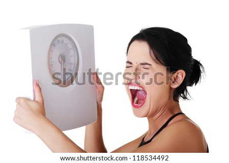 Frustrated woman with scale, isolated on white - stock photo