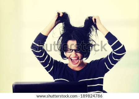Frustrated woman working on laptop - stock photo