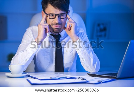 Frustrated young  aged businessman sitting at office desk - stock photo