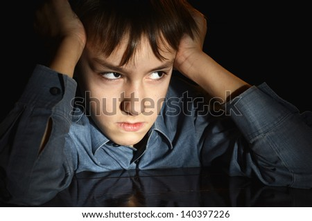 frustrated young boy on a black background - stock photo
