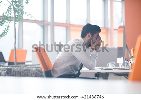 frustrated young business man working on desktop  computer at modern startup office interior