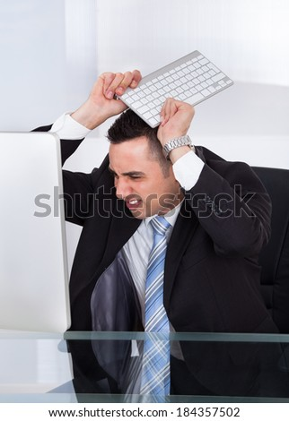 Frustrated young businessman throwing computer keyboard at office desk - stock photo