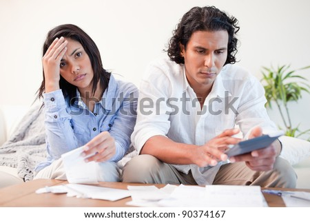 Frustrated young couple doing their calculations in the living room - stock photo