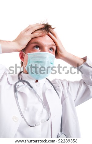 Frustrated young doctor with hands on head wearing surgical mask.
