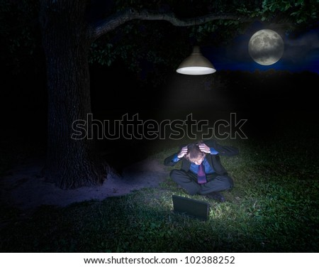 Frustrated young man with laptop in forest under the lamp at night - stock photo