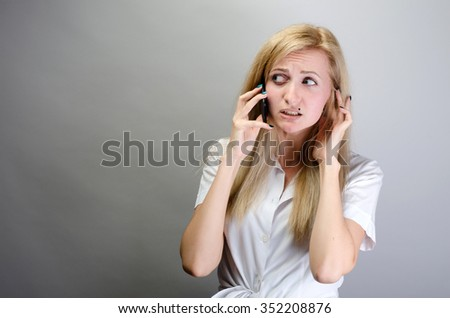 frustrated young woman talking on mobile phone, touching face, closing ear with hand, bad news, cellular connection concept - stock photo