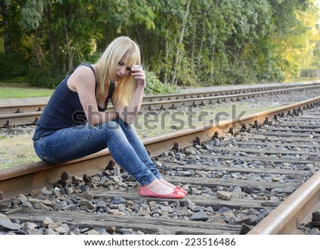 frustrated young woman with cigarette sitting on rail track - stock photo