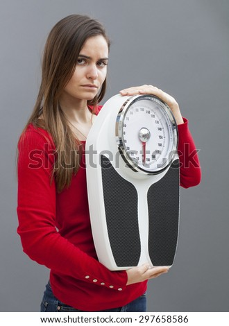 frustrated young woman with weighting scale in hands for concept of weight loss or weight control - stock photo