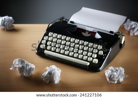 Frustration stress and writers block with old typewriter on desk and crumpled paper ball - stock photo