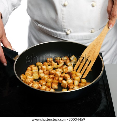 Frying croutons - stock photo