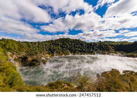Frying Pan Lake, Waimangu Volcanic Valley, a steaming hot lake in the new born volcanic Echo crater with acid mineral rich water. Beautiful sky, wide angle view from above. New Zealand, Rotorua area. - stock photo