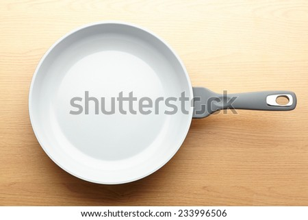 Frying pan on wooden table background - stock photo