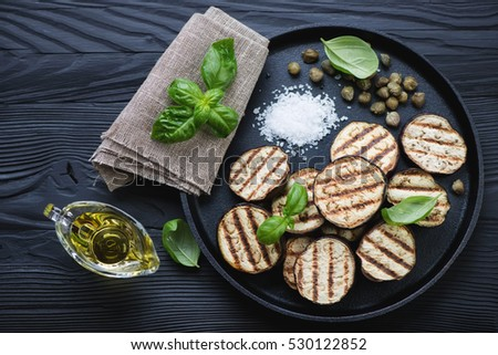 Frying pan with bbq aubergine slices, capers, sea salt and basil over black wooden background, high angle view