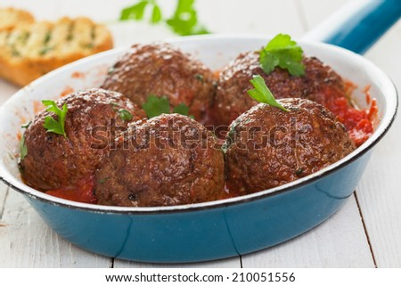 Frying pan with five savory Italian meatballs in spicy tomato sauce garnished with fresh basil, closeup low angle view - stock photo