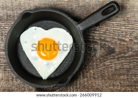 Frying pan with fried egg in shape of heart on old wooden background - stock photo
