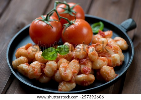 Frying pan with gnocchi in tomato sauce, selective focus - stock photo
