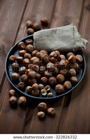 Frying pan with hazelnuts over wooden background, studio shot