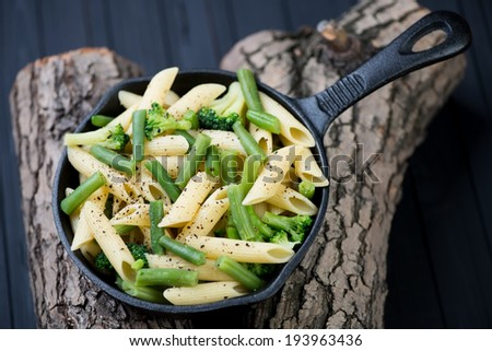 Frying pan with penne pasta and vegetables, above view - stock photo