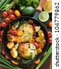 Frying pan with roasted chicken, vegetables, herbs and fruits. Shallow dof. - stock photo