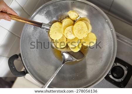 Frying the big slice potato in a wok - stock photo