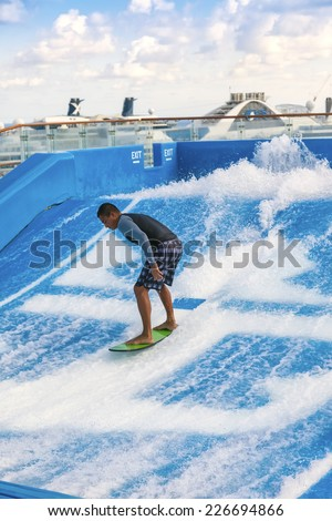 FT. LAUDERDALE, FL - JAN. 12, 2013:  Man surfing on the FlowRider aboard the Oasis of the Seas.  Royal Caribbean offers this activity to all it's guests aboard it's Freedom and Oasis-class ships.   - stock photo