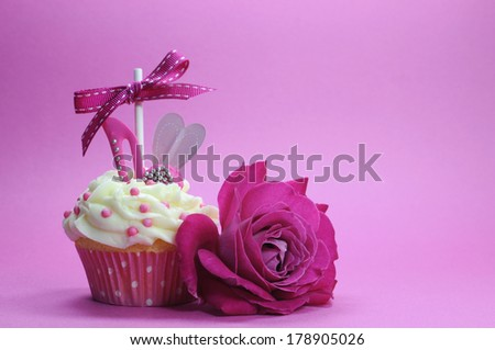 Fuchsia pink theme cupcake with shoe and heart decoration and beautiful rose, for International Womens Day, Mothers Day, female birthday or bridal shower. - stock photo