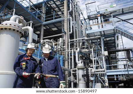 fuel and gas refinery with two engineers in foreground